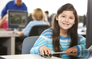 girl-sat-at-computer-smiling